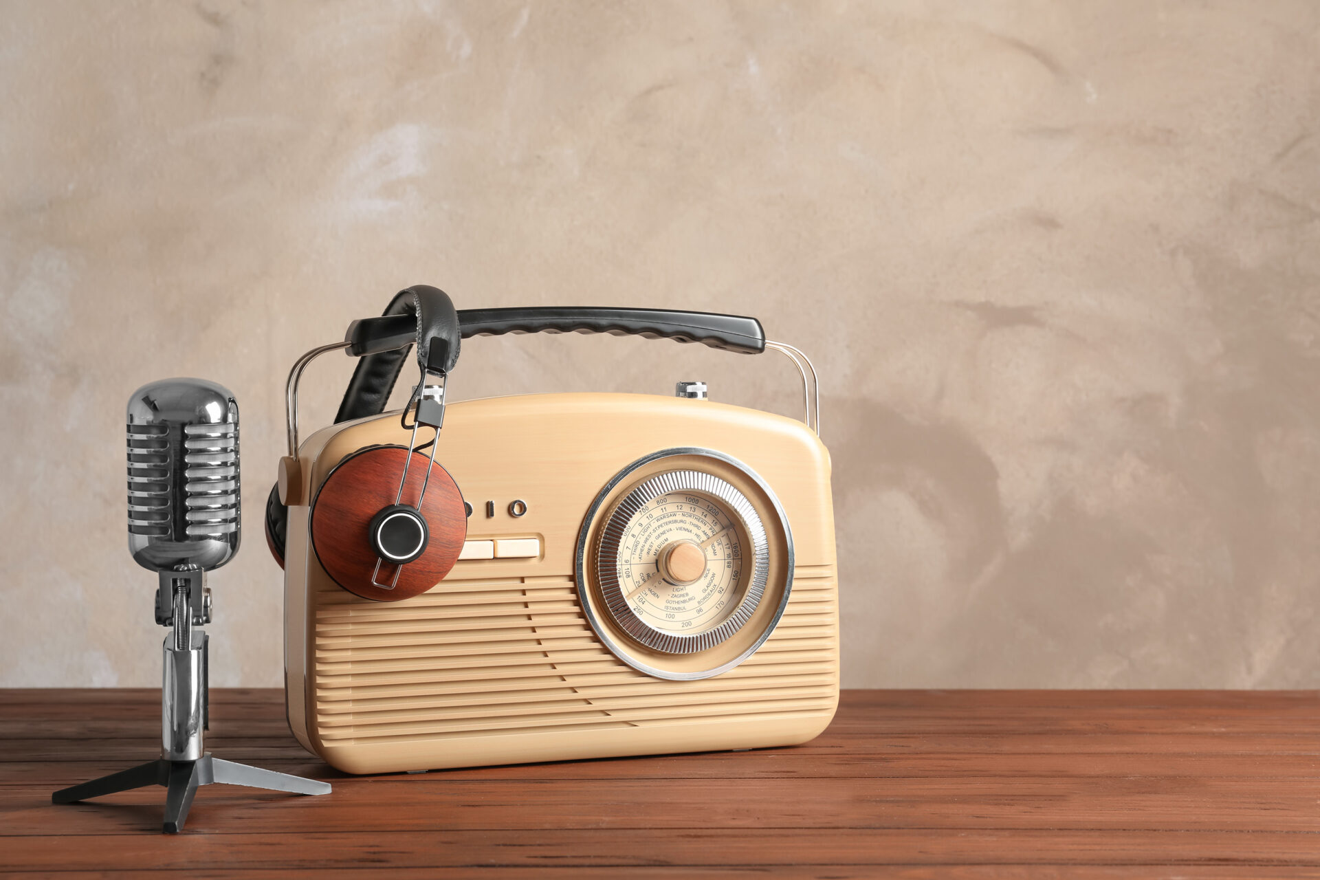 Retro radio, microphone and headphones on table against light wall